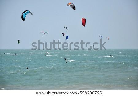 MUI NE, VIETNAM - MARCH 5, 2013: Kite surfers kitesurfing on the sea against heavy wind in the South China sea, Vietnam