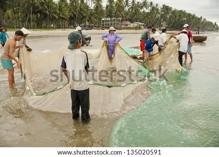 MUI NE, VIETNAM - NOVEMBER 3: Unidentified Vietnamese people pull their seine out on the beach in Mui Ne, Vietnam on November 3, 2008. For most of Vietnamese seafood is main source of livelihood. - stock photo