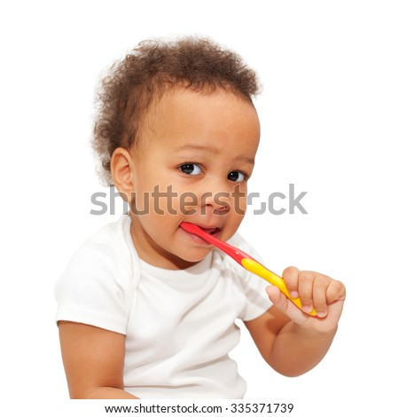 Mulatto black baby brushing teeth. Isolated on white background. - stock photo
