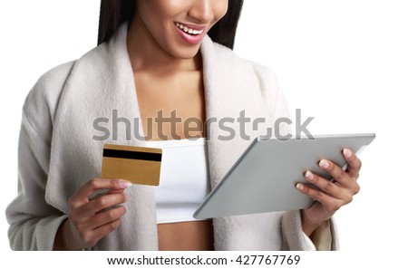 Mulatto black woman holding digital tablet computer and pay from credit card. Close-up view. Isolated on white - stock photo