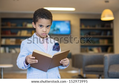 Mulatto boy in a striped jacket with a book in hand