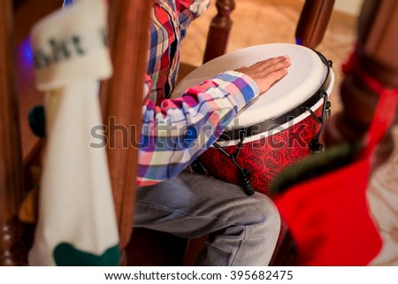Mulatto child playing percussion drum. Boy plays djembe on stairs. Lively Christmas music at home. Little musician's holidays. - stock photo