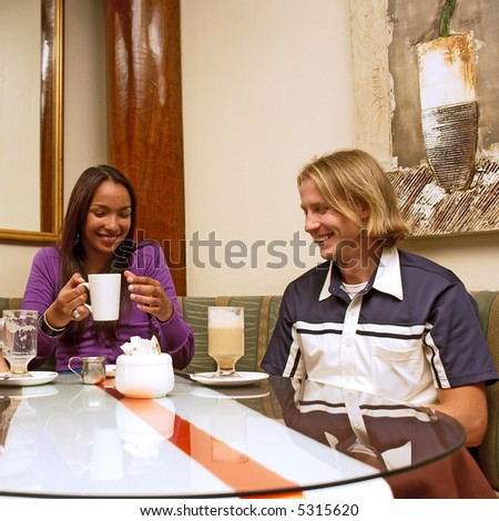 Mulatto girl and blond man are drinking coffee in a restaurant. Shot in Western Cape, South Africa.