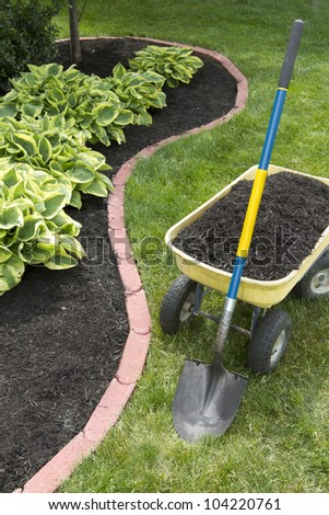 Mulch bed around the house and wheelbarrow along with a shovel. - stock photo