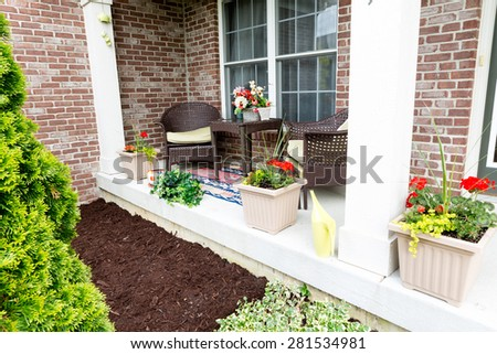 Mulching flowerbeds around the house with a freshly mulched bed alongside an open-air patio decorated with ornamental flowers - stock photo