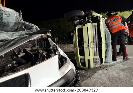 MULES, ITALY - JUNE 16, 2014: A police man giving first aid to a injured motorist after a serious collision car crash accident in the night on June 16, 2014 - stock photo