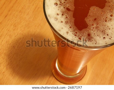 mulled beer in winter time or cold beer in summer time, beer in glass,  focus on beer, wood background, - stock photo