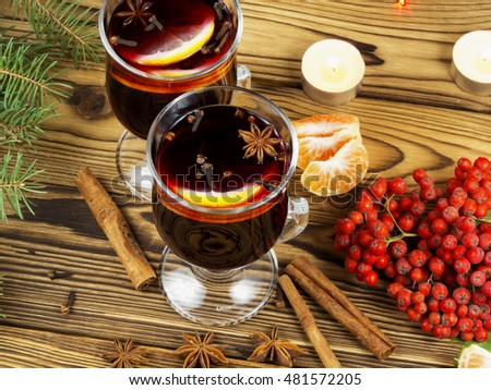 Mulled red wine with spices on wooden table