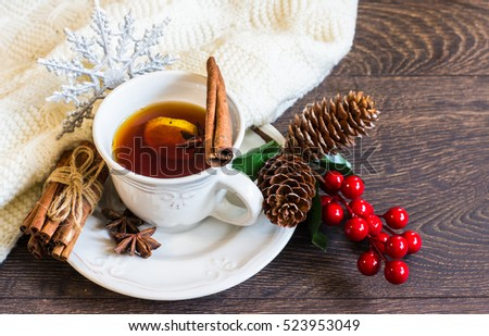 Mulled tea with spices and festive Christmas decorations on dark wooden background with copyspace