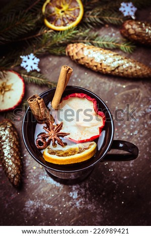 mulled white wine with dried fruit, cinnamon and anise on winter decoration wooden background - stock photo