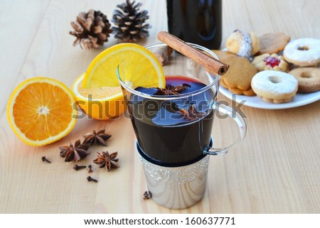 Mulled wine in glass mug, spices, cookies and orange on wooden table. Shallow DOF. - stock photo