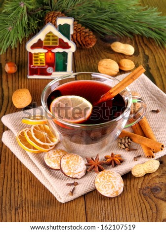 Mulled wine in glass with cinnamon stick, candle and sweets, close up - stock photo