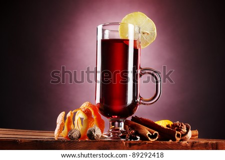 mulled wine in the glass, spice and lemon on purple background - stock photo