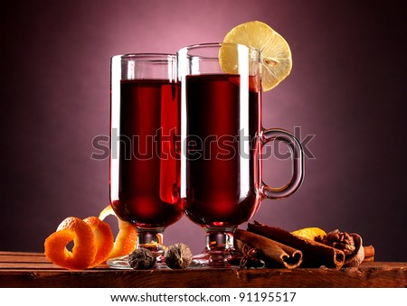 mulled wine in the glasses, spice and lemon on purple background - stock photo