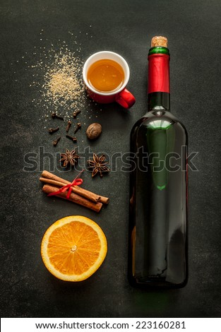Mulled wine recipe ingredients on black chalkboard - christmas or winter warming drink. Bottle of wine, honey, orange, cinnamon sticks, anise, nutmeg, cloves and sugar from above. - stock photo