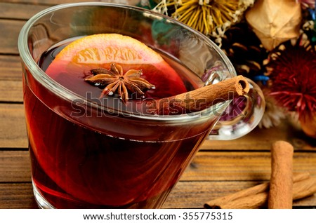 Mulled Wine with dried flower decoration on wooden table - stock photo