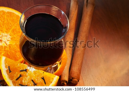Mulled wine with orange and spices on the table - stock photo