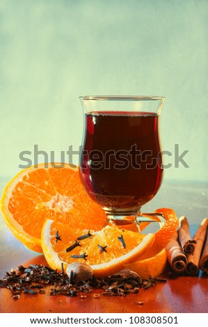Mulled wine with orange and spices on the table against green background - stock photo