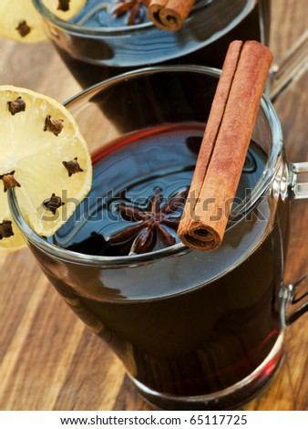 Mulled wine with slice of lemon and spices. Shallow dof. - stock photo