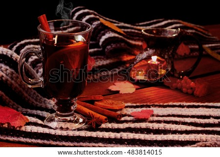 Mulled wine with spices (cinamon, star anise) and dried lemon on knitted scarf .Fallen leaves. Autumn theme.Selective focus.Aroma lamp.Light of candle