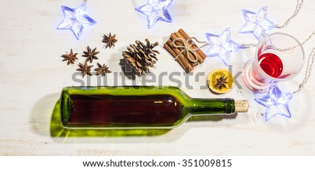 Mulled wine with spices cinnamon, anise, orange and christmas decoration lights - stock photo