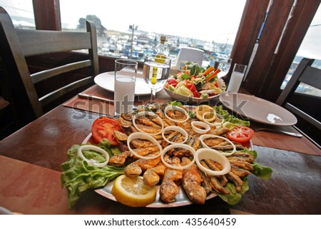 Mullet fish (Turkish: Barbun) with salad and raki on the restaurant table. - stock photo