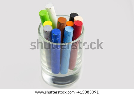 multi color chalk Oil pastel in glass on white background - stock photo