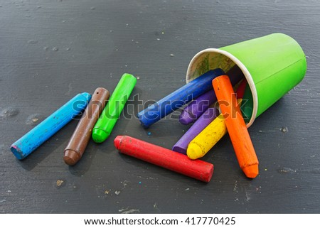 multi color chalk oil pastel in green cup on black background - stock photo