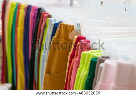 Multi Color Clothes Hanging in Wardrobe showcase, Shallow depth of Field.  Focus on Brown Pants