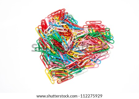Multi color paper clips arranged in heart shape on isolated white background. - stock photo