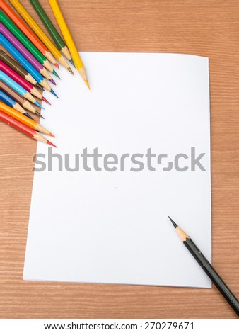 Multi-color pencil with blank white paper on wooden background - stock photo