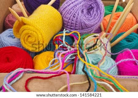 multi-colored balls of wool knitting yarn in a cardboard box - stock photo