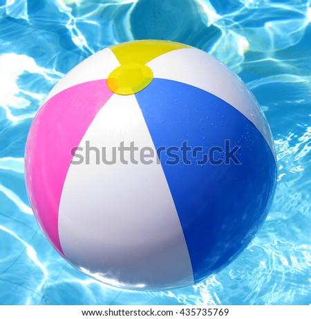 Multi colored Beach ball in swimming pool  - stock photo