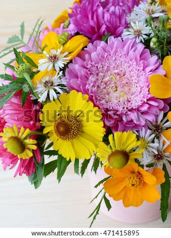 Multi-colored bouquet of different flowers in the pot on a wooden background