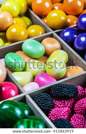 multi colored candy and chewing gum in a wooden box. Focus in the middle of the frame - stock photo