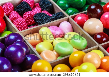 multi colored candy and chewing gum in a wooden box. Focus on the top of the frame - stock photo