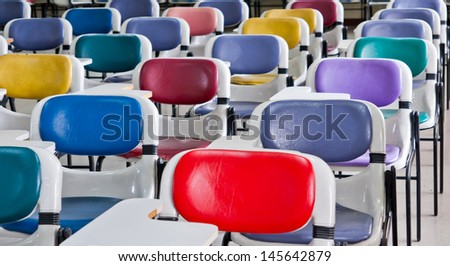 Multi colored chairs arranged in the room - stock photo