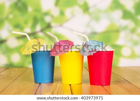 Multi-colored disposable paper cups and straws on abstract green background. - stock photo
