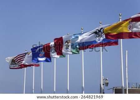 Multi-colored flags flying from pier in Santa Barbara, California - stock photo