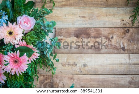 Multi-colored flowers on a wooden board.