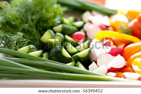 Multi-colored fresh vegetables, cut, on a plate - stock photo