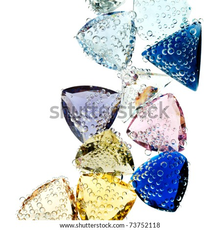 Multi-colored gems falling into water isolated on white. - stock photo