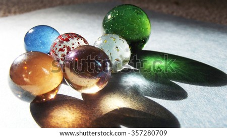Multi colored glass marbles shadows - stock photo