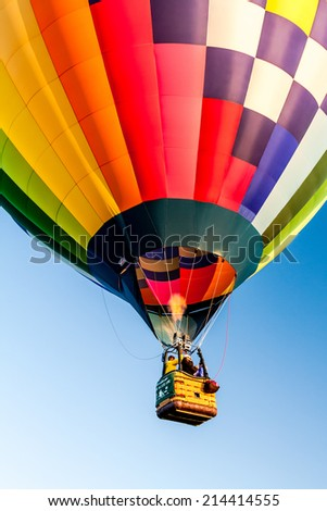 Multi-colored hot air balloon taking off at balloon festival - stock photo