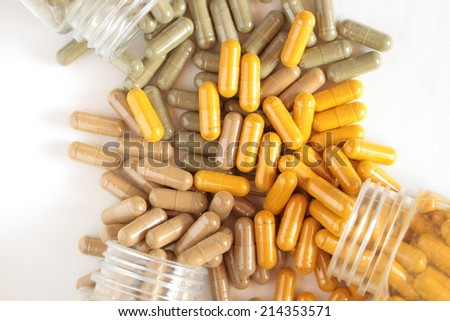 Multi colored medical pills spilling out of a prescription bottles. - stock photo
