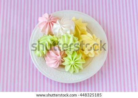 Multi-colored meringue on a white saucer on the background of the tablecloth
