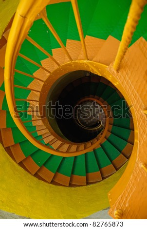 Multi-colored metal spiral staircase in old lighthouse - stock photo