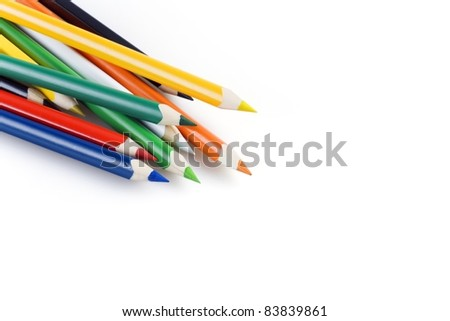 Multi colored pencils in a corner on a white background - stock photo