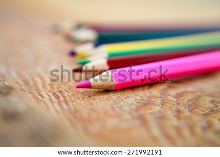 Multi-colored pencils on a wooden background - stock photo