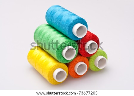 multi-colored rainbow threads for sewing - stock photo